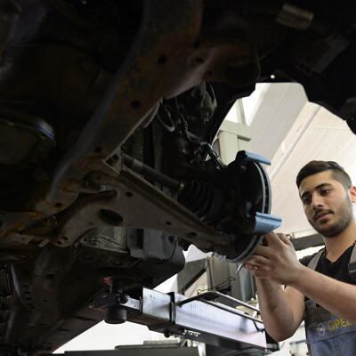 TO GO WITH AFP STORY by MATHILDE RICHTER - Picture taken on July 14, 2015 shows Syrian refugee George Romanos working on a car at a workshop in Bobingen, southern Germany, on July 14, 2015. Like a growing number of German employers, garage-owner Robert Menhofer has decided to give a young refugee a chance and is lavish in his praise for George Romanos, a young trainee from Syria.     AFP PHOTO / CHRISTOF STACHE